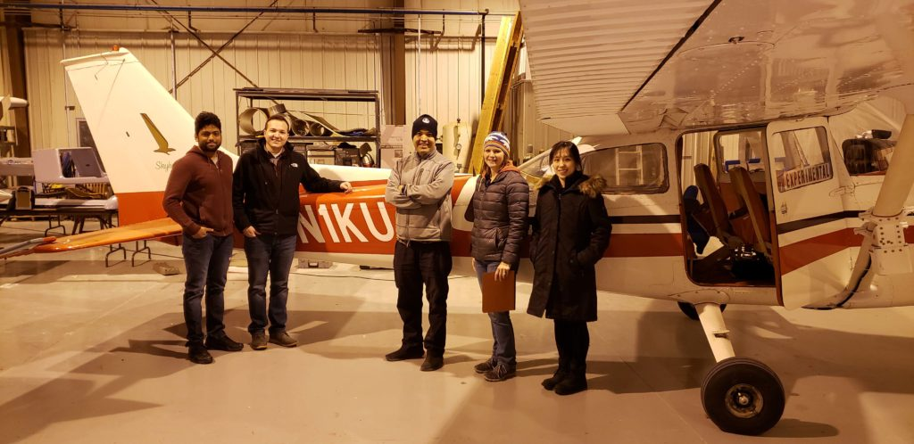 Students stand in front of the specially equipped Cessna 172