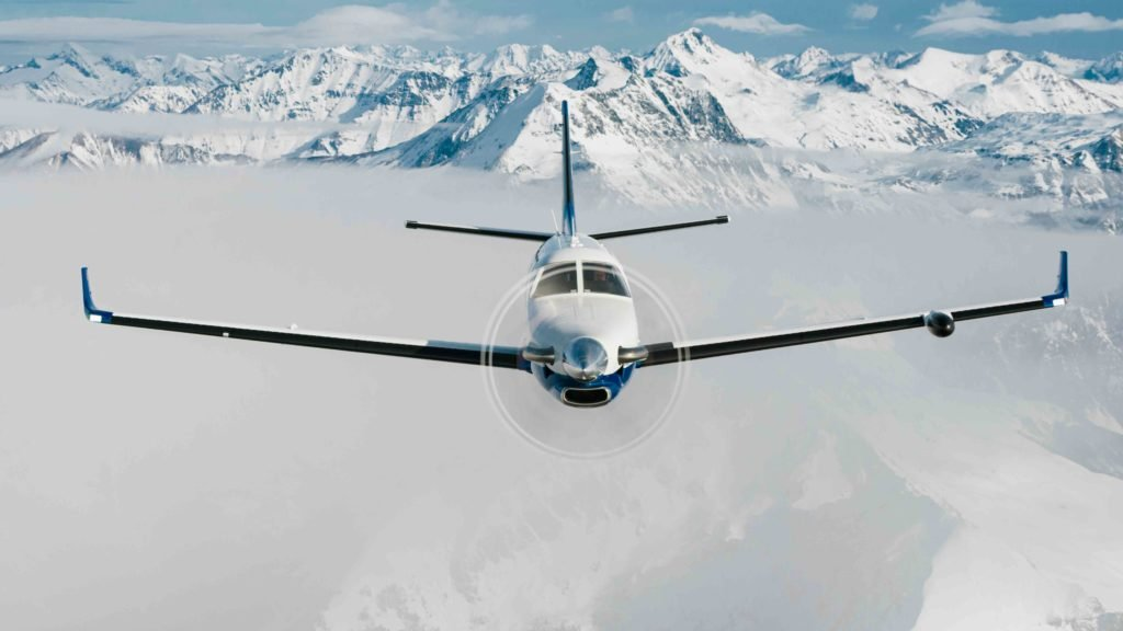 Daher TBM 940 aircraft in-flight with mountains in background