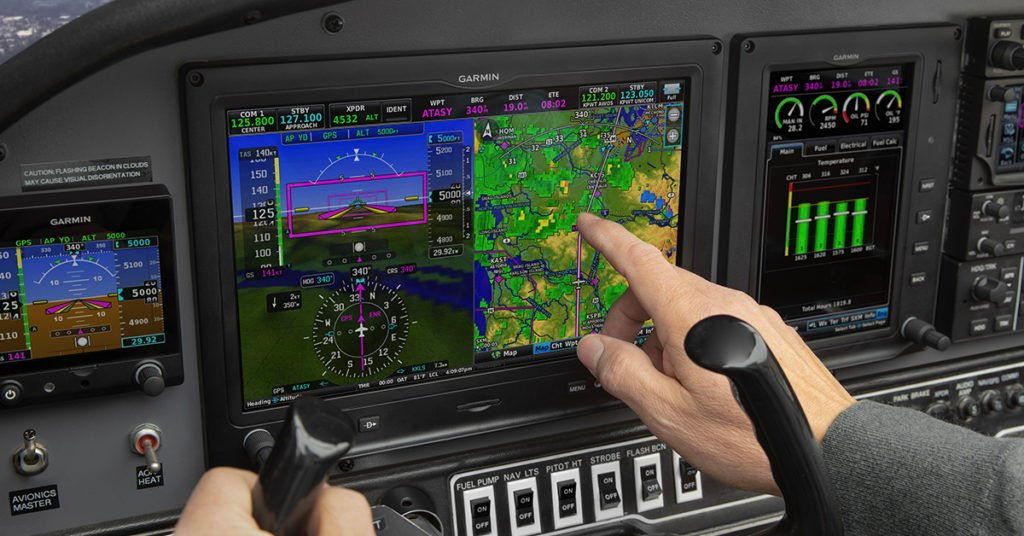 Pilot interacting with G3X Touch in cockpit of aircraft