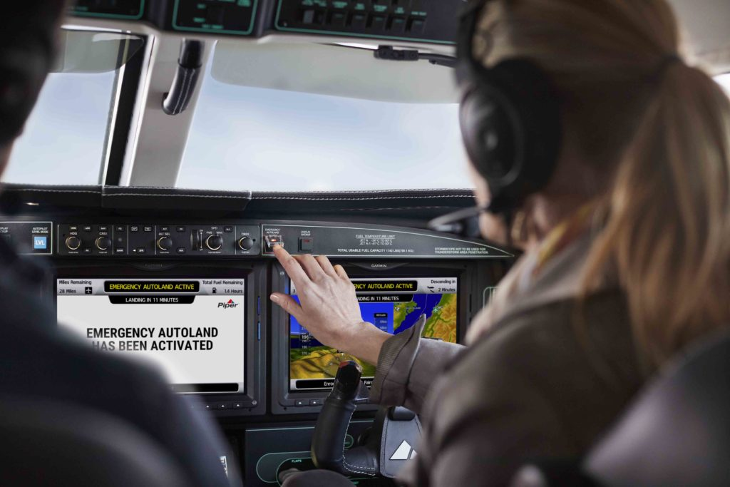 Passenger selecting Autoland button in Piper M600 SLS, Autoland activation screens displayed on G3000
