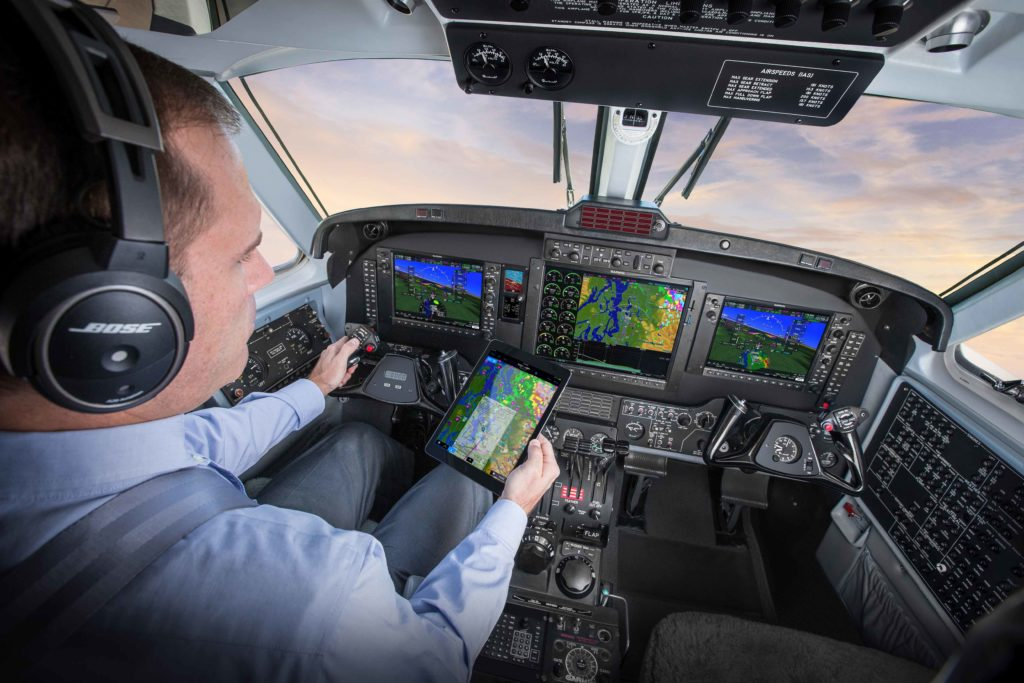 King Air flight deck featuring G1000 NXi, pilot holding iPad