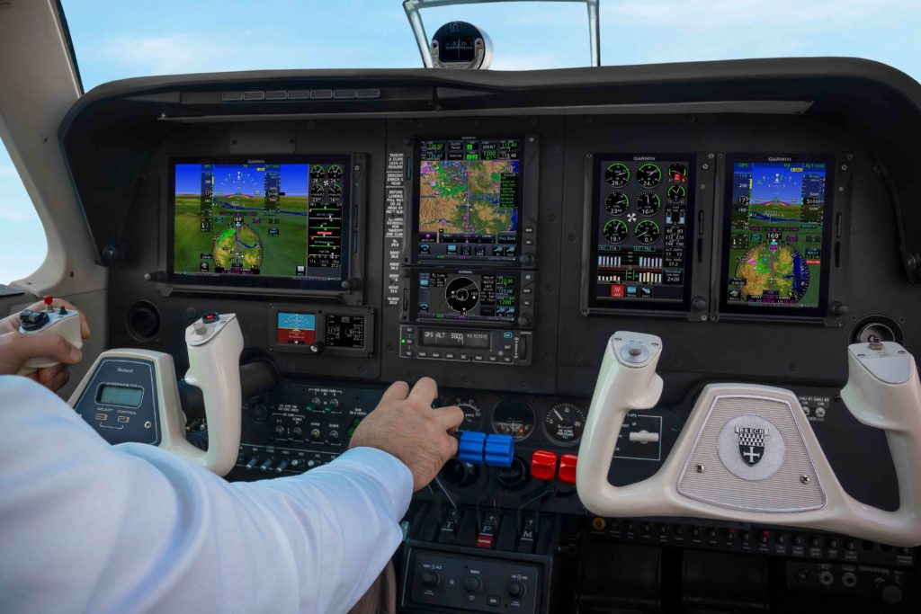 Pilot flying airplane with hand on yoke and throttle, Smart Rudder Bias active