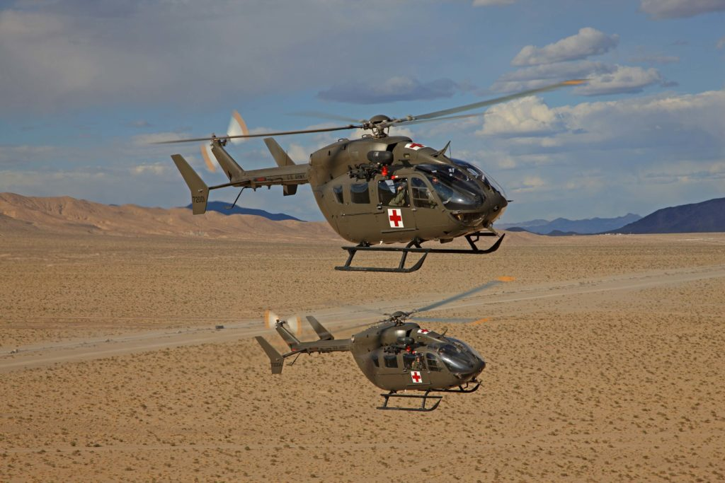 Two Airbus helicopters flying in formation over desert